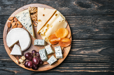 Assortment of cheese with fruits and grapes on a wooden table. vignetting as an artistic effect Stock Photo