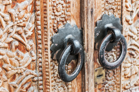 Old handles on the door with carved patterns and ornaments Stock Photo