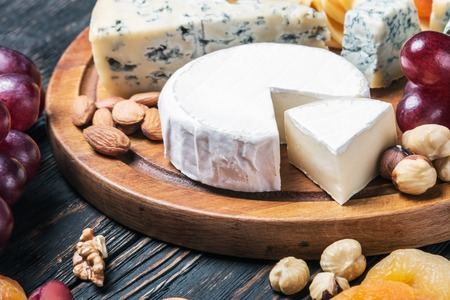 variety of cheeses with grapes and dried fruits on the table Stock Photo