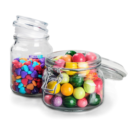 jelly beans: different color candy and gum in glass jars isolated on white background