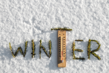 thermometer with sub-zero temperatures in the snow in the winter. Word winter from fir branches
