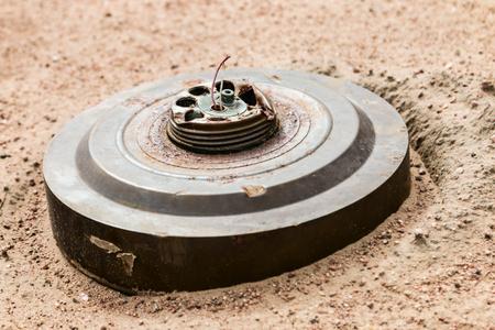 oude anti-tankmijn begraven in het woestijnzand Stockfoto