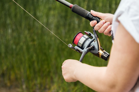 female hands holding a fishing rod feeder, and rotate the fishing reel. Shallow depth of field, soft focus