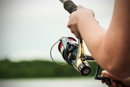 twist: female hands holding a fishing rod and twist the handle of the fishing reel. Shallow depth of field, soft focus