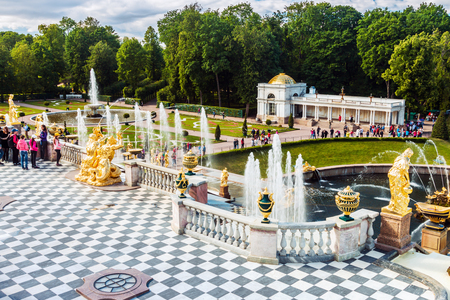 ST PETERSBURG, RUSSIA - July 08, 2017: Tourists in Peterhof the fountains of the Grand Cascade. The Peterhof Palace included in the UNESCOs World Heritage List Editorial