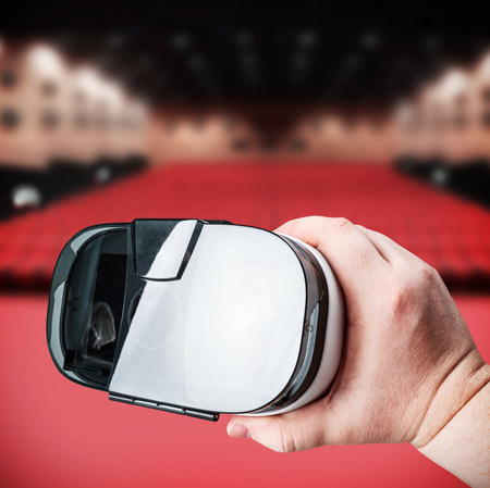 virtual reality simulator: hand holds virtual reality glasses on the background of cinema