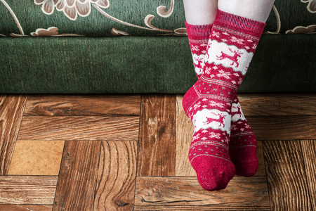 female legs in Christmas socks sitting on sofa Stock Photo