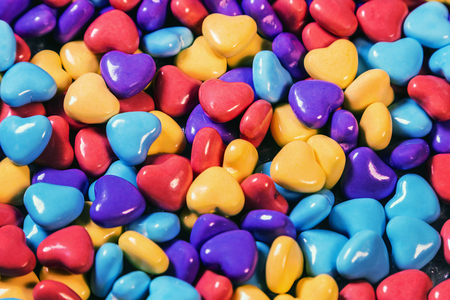 chewable candies of different colors in the shape of hearts background