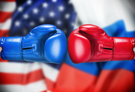 Boxing gloves red and blue on the background of the flag of the United States and Russia. symbolizes a Difficult period of relations between the United States and Russia.