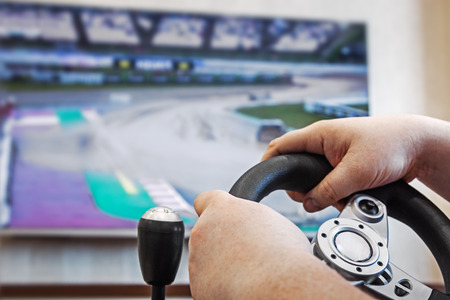 hands holding the steering wheel of the game console. Modern game technologies Stock Photo