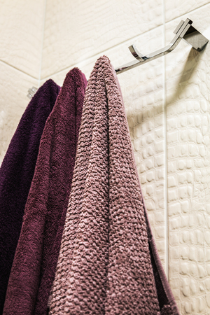 different colors of towels hang on a hanger in the bathroom Banque d'images
