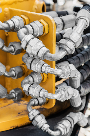 pipes and the hydraulic system of the tractor or excavator.Focus on the left side of the frame on the pipes 스톡 콘텐츠
