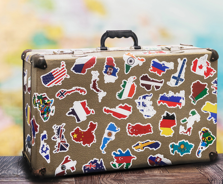 old suitcase with stikkers on the floor against the backdrop of a world map Stock Photo