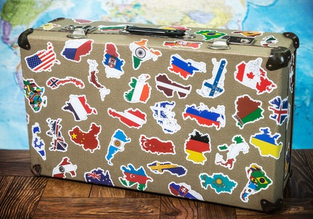 old suitcase with country flag stickers from traveling around the world on the floor. World map background Stock Photo - 111602314