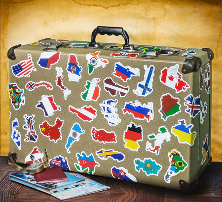 retro suitcase with stickers on the floor against an old wall 写真素材