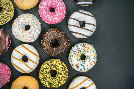 assorted donuts with different fillings and icing on a black background. top view