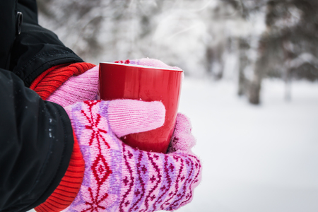 hands in Christmas mittens holding a mug of hot drink in the Park. space left for your text Foto de archivo