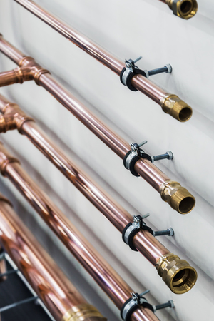 copper pipes and fittings for carrying out plumbing work. focus in the lower part of the frame at the connection with thread