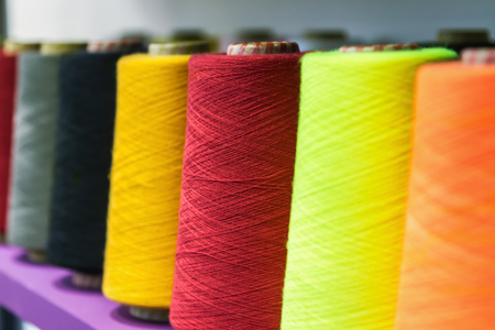 different color spools of thread for the textile industry on the shelf