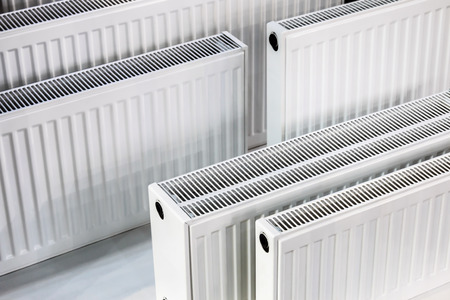 many metal radiators of different sizes. background of heating batteries Stock Photo