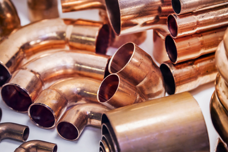 copper pipes of different diameter and sizes and adapters for carrying out plumbing works Фото со стока