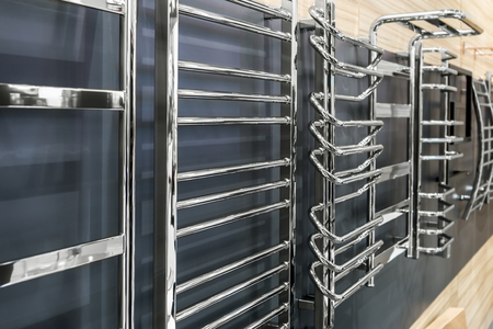 chrome heated towel rails and radiators of different types and designs on the wall