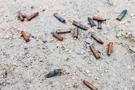 lots of old rusty gun casings on the ground. Consequences and remnants of war Stock Photo