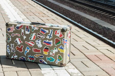 tourist suitcase with stickers of countries of the world and continents on the station platform