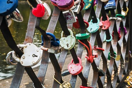 Moscow, Russia-October 5, 2019: various locks of the newlyweds hang closed on the fence of the bridge. Moscow Botanical garden.