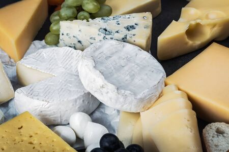 different varieties and types of cheese with fruit, nuts and baguette Imagens