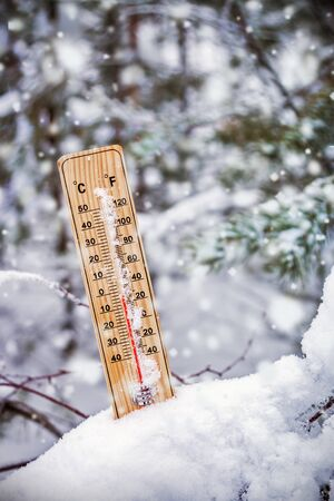 thermometer with plus temperature sticking out of the snow in the winter forest Banque d'images - 135493320