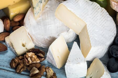types of different cheese on the table with nuts, dried apricots, grapes, etc. Stock fotó