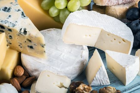 types of different cheese on the table with nuts, dried apricots, grapes, etc. Stock fotó - 135949845