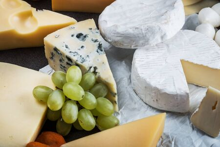 many different types of cheese with nuts, grapes and dried fruits