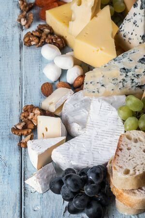 many different types of cheese with nuts, grapes and dried fruits Stock fotó - 136385136