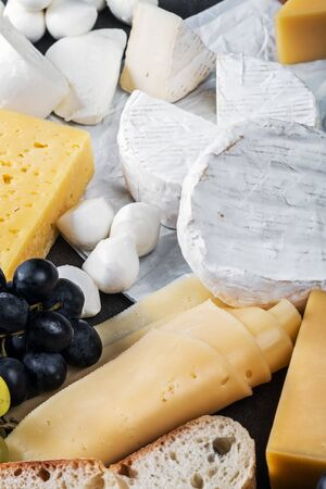 different assortment of cheeses with fruit, nuts and bread is on the cutting Board Foto de archivo