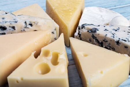 assortment of soft, hard, rennet and brine cheeses on a cutting Board