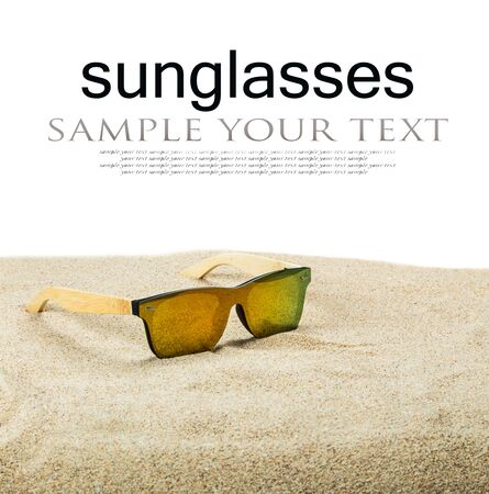 sunglasses with blue glasses on the sand in the desert isolated on a white background. Text delete