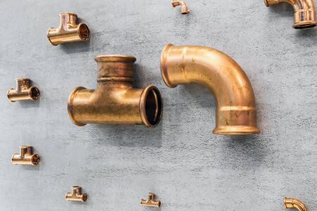 samples of copper pipes and fittings. Copper pipes, pipes and various parts on the wall