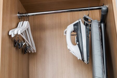 wardrobe with wooden hangers without clothes and built-in Ironing station