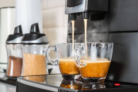 two glass cups with hot coffee from the coffee machine in the kitchen interior Stockfoto