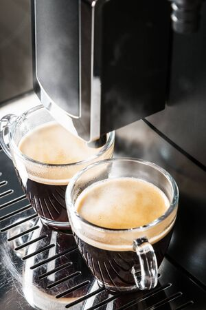 two glass cups of hot espresso are being prepared in the coffee machine