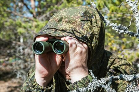 spy or scout looks through binoculars and scouts the area Banque d'images