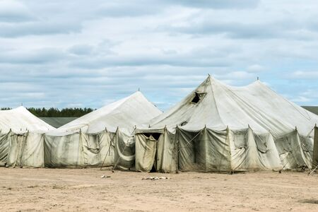 old soldiers  canvas tents torn in the wind in the field. Tent city on military exercises
