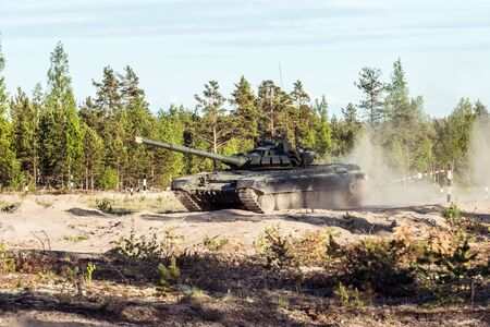 battle tank rides on a dusty road in the forest. Advanced tank of the Russian army t-90