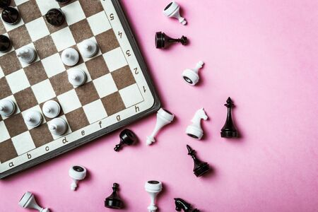 chessboard and chess pieces in a played game on a pink background