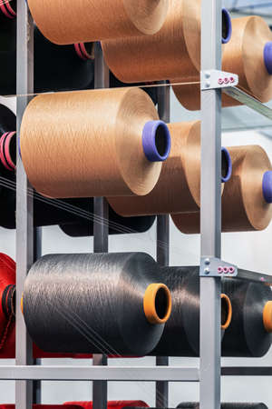 bobbins with threads of different colors on the shelves of a clothing factory Foto de archivo