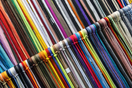 different colors of laces or rope on the shelves of a clothing factory Foto de archivo