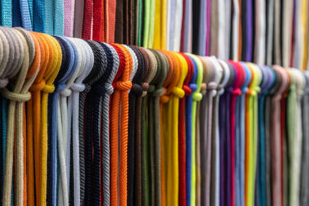 different colors of laces or rope on the shelves of a clothing factory or production