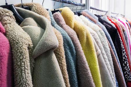 Faux fur coats on a hanger in the store Foto de archivo